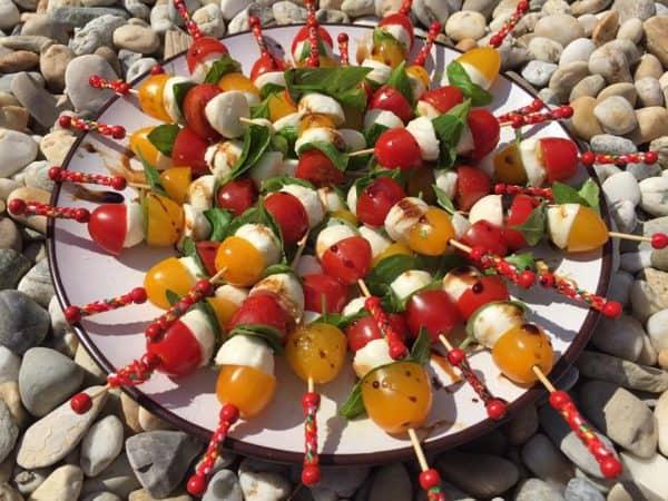 CAPRESE ŠPÍZIKY: Ingrediencie: červené/žlté rajčiny, mini mozarella, bazalkové listy. Postup: Rajčiny, mozarellu prekrojíme napoly a striedavo napichujeme na spajlu spolu s bazalkou. Hotové špízy posolíme, polejeme olivovým olejom a krémovým balsamicom.