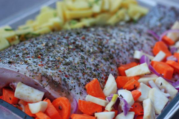 Koreňovú zeleninu si ošúpeme a nakrájame. Všetku okrem zemiakov si v miske zmiešame, posolíme, posypeme rascou, olivovým olejom a prenesieme na jednu stranu pekáča, po jednom boku ryby. Ošúpané a nakrájané zemiaky tiež posolíme, posypeme rascou, čerstvou pažítkou, olivovým olejom a prenesieme na druhý bok ryby. Na zeleninu položíme cca 4 plátky masla.